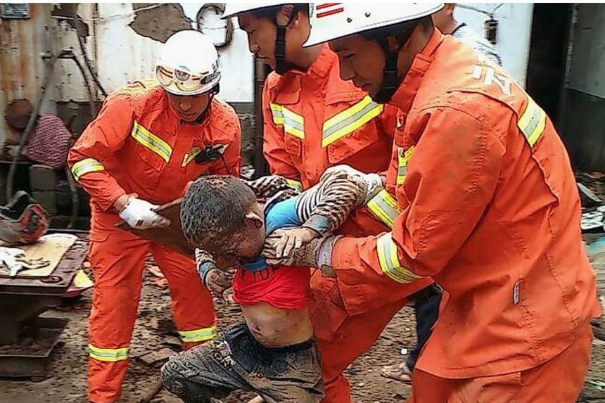 Rescue workers evacuate a boy dug out from under the debris of collapsed houses,after a magnitude 6.3 earthquake hit Longtoushan town, Ludian county, Zhaotong, Yunnan province, August 4, 2014.An intense rescue operation was under way in C