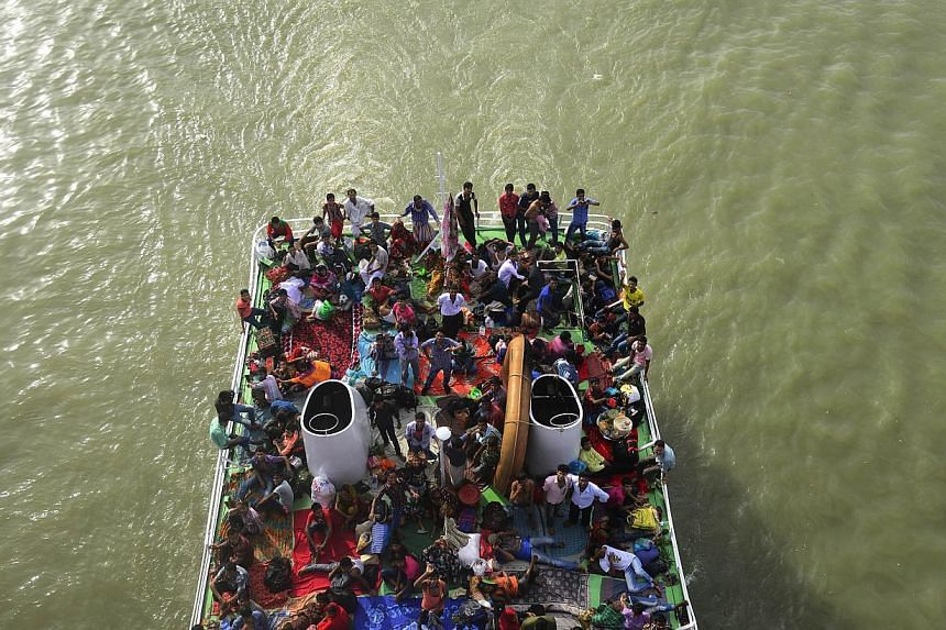 Bangladeshis ride on packed ferries as they rush home to be with their families in their respective villages ahead of the Eid al-Fitr festival, near the Sadarghat ferry terminal on the outskirts of Dhaka on July 27, 2014. An overloaded ferry car