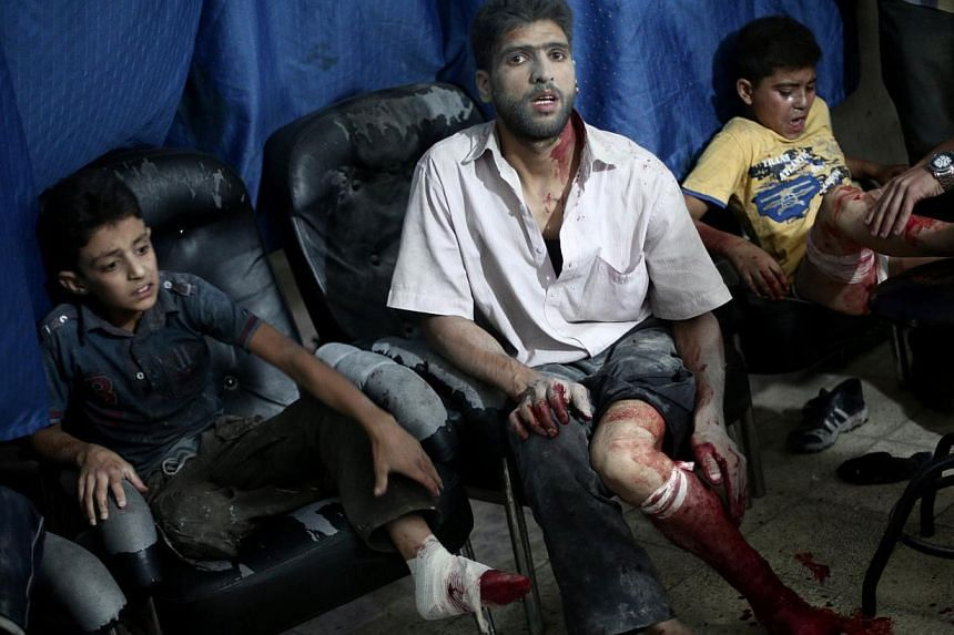 Victims wait to be treated by medics at a makeshift hospital following reported shelling by Syrian government forces in Douma, north-east of Damascus, on August 3, 2014. At least 32 people were killed in Syrian regime air raids on two rebel-held town