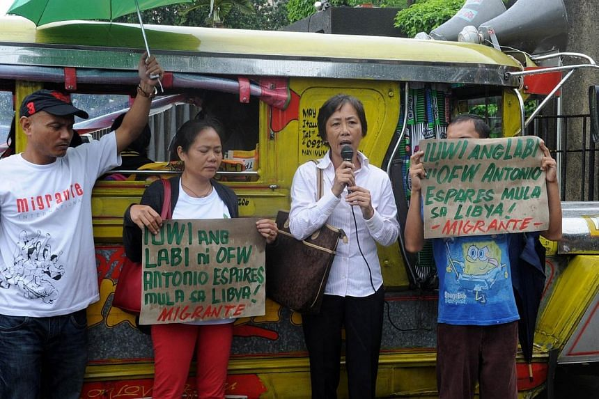 Maribel Espares (2nd from left), widow of the Filipino worker beheaded by armed men in Libya last month, joins a protest at the Department of Foreign Affairs in Manila on August 5, 2014, to call for the speedy repatriaton of the estimated 11,000 Fili