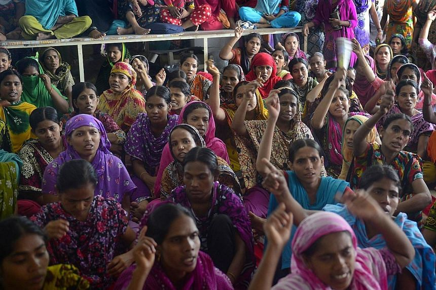 Bangladesh garment workers from the Tuba Group shout slogans as they protest unpaid salaries, in Dhaka on Aug 2, 2014. -- PHOTO: AFP