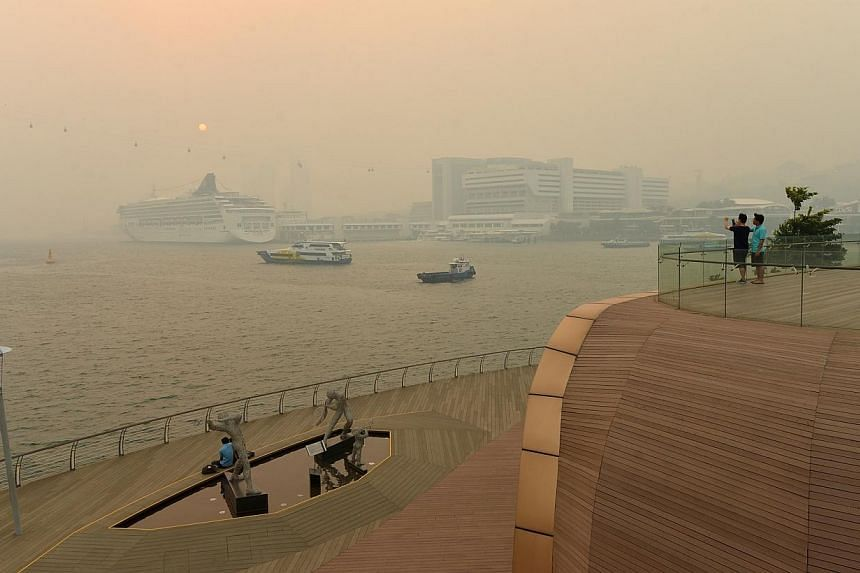 People taking in the view along the Sentosa bridge at 6pm on June 19, 2013, unfazed by the haze.The penalties in a new law to combat haze could rise if future reviews find them insufficient, said Environment and Water Resources Minister Vivian