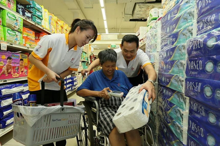 Ms Ng May Chan (in blue), 57, went on a shopping trip sponsored by NTUC FairPrice as part of their 41st anniversary celebrations. Ms Ng May Chan, 57, chose $50 worth of groceries, including instant noodles, bread and tuna, from the FairPrice Fin