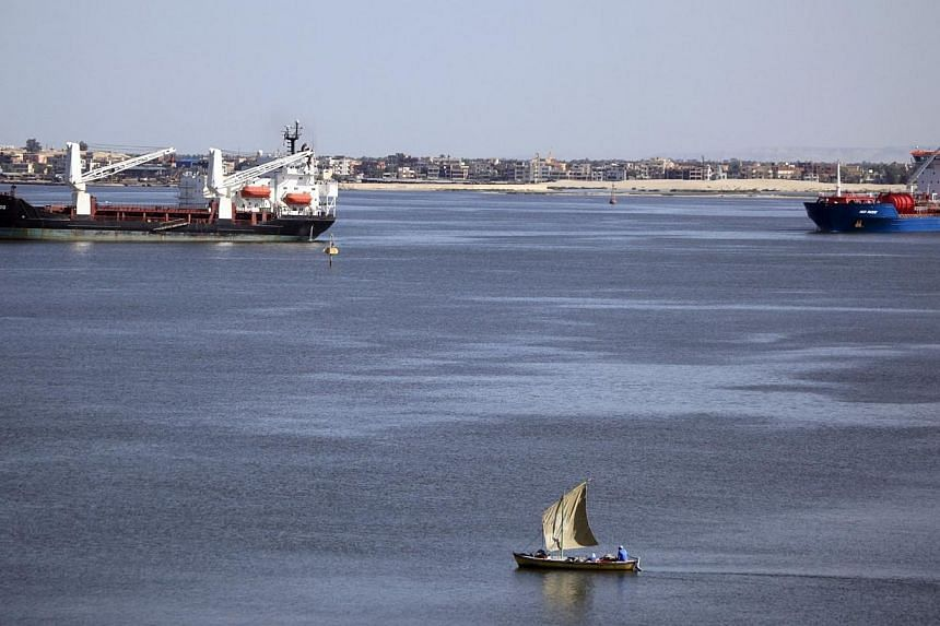 A fisherman travels on a boat near container ships in the Suez Canal, near Ismailia port city, northeast of Cairo on May 2, 2014.Egypt plans to build a new Suez Canal alongside the existing 145-year-old historic waterway in a multi-billion doll