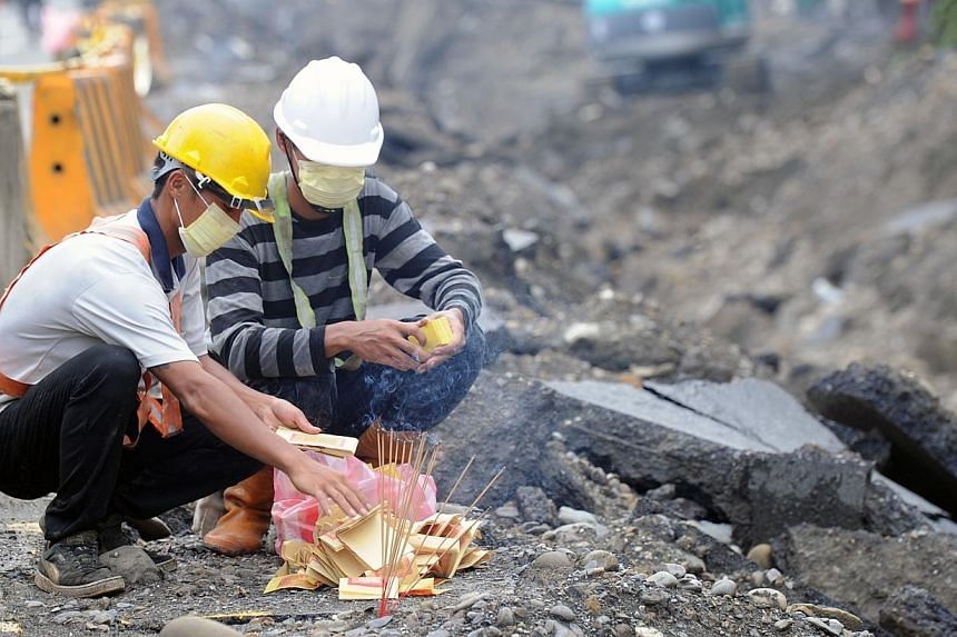 Rescue workers burn ghost money to the victims of the gas explosion in the southern Taiwanese city of Kaohsiung on Aug 2, 2014.Taiwan authorities raided the offices of two firms linked to massive gas explosions that killed 28 people as the isla