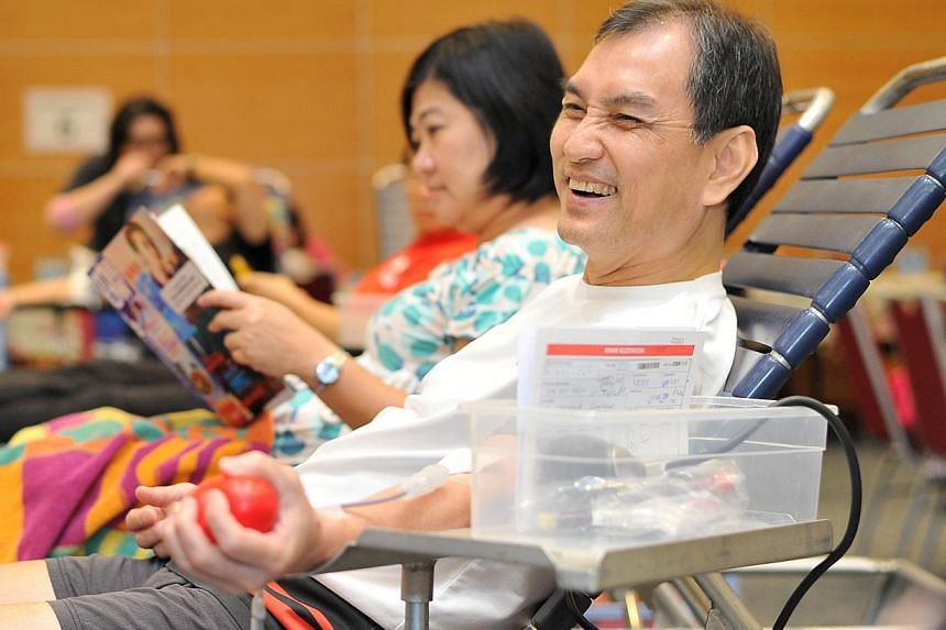 Mr Lim Jit Siew, 59, Financial Consultant, at SPH Red Apple Day, on Aug 05 2014.-- ST PHOTO: LIM YAOHUI FOR THE STRAITS TIMES