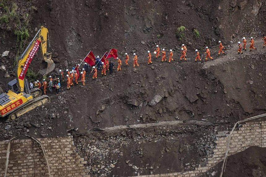 A group of rescue workers walk through a collapsed road at an earthquake hit area in Ludian county, Zhaotong, Yunnan province on Aug 5, 2014. -- PHOTO: REUTERS
