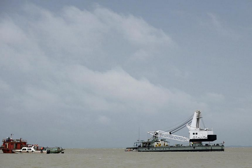 Bangladeshi rescue teams search the waters where an overloaded ferry capsized the day before in the Padma river in Munshiganj, some 30km south of the capital Dhaka, on Aug 5, 2014. -- PHOTO: AFP