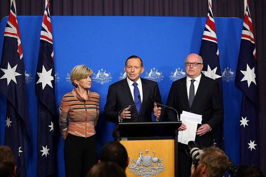 This picture released by the Australia Prime Minister Office on Aug 5, 2014 shows Prime Minister Tony Abbott (centre) speaks at a joint press conference with foreign minister Julie Bishop and Attorney General George Brandis (right) in Canberra. -- PH
