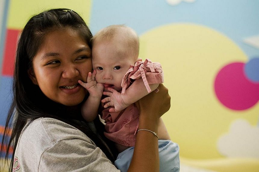 Thai surrogate mother Pattaramon Chanbua (left) holds her baby Gammy, born with Down Syndrome, at the Samitivej hospital, Sriracha district in Chonburi province on Aug 4, 2014. -- PHOTO: AFP