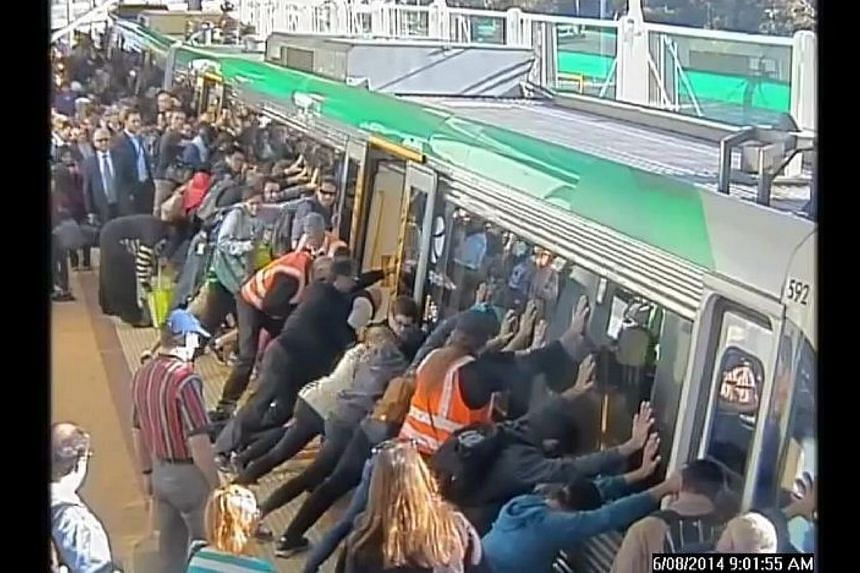 "Dozens of Australians tilted a train Wednesday to free a commuter whose leg was trapped between a carriage and a platform, with authorities praising their efforts as an example of ""people power"". -- PHOTO: PUBLIC TRANSPORT AUTHORITY OF WESTERN AUSTRA"