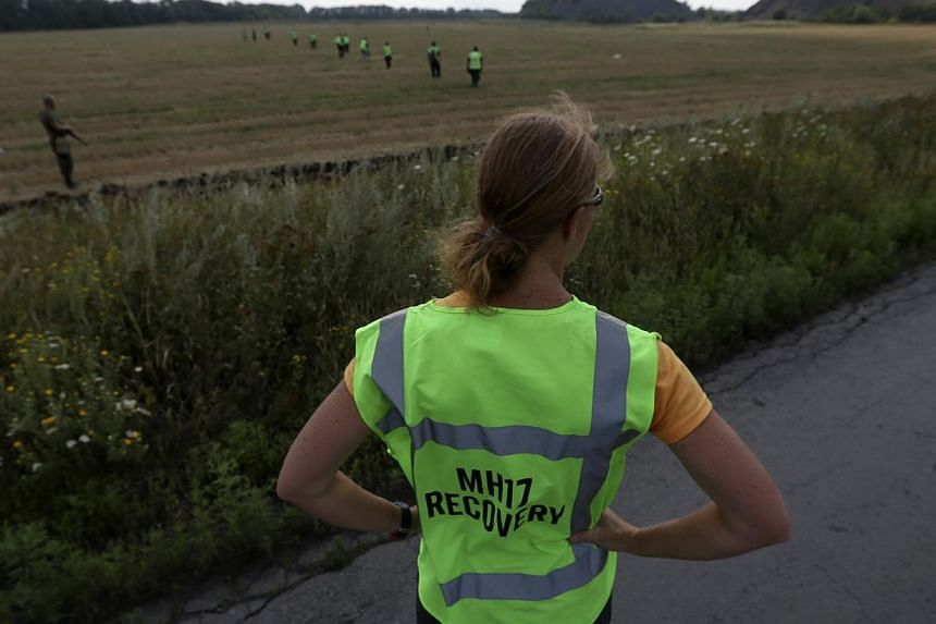 A forensic expert watches as recovery work continues at the site of the downed Malaysian airliner MH17 near the village of Rozsypne in the Donetsk region on Aug 4, 2014. Dutch, Australian and Malaysian investigators at the eastern Ukraine crash