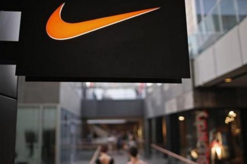 People walk past a Nike shop under the company logo at the Sanlitun shopping area in central Beijing. -- PHOTO: REUTERS