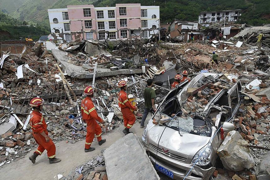 Rescue workers walk past debris of houses at an earthquake zone in Ludian county, Zhaotong, Yunnan province on Aug 5, 2014. -- PHOTO: REUTERS