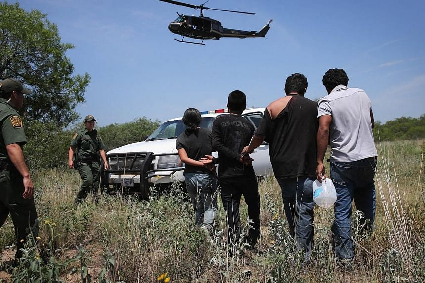 US Customs and Border Protection agents take undocumented immigrants into custody on July 22, 2014 near Falfurrias, Texas.As President Barack Obama considers sidestepping Congress to loosen US immigration policy, a Reuters/Ipsos poll shows Amer