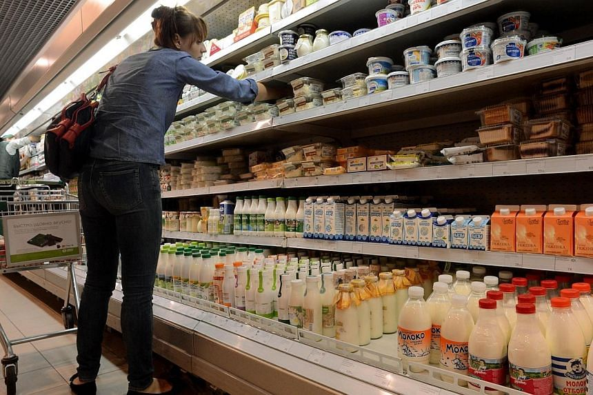 """A file picture taken on Aug 5, 2013 shows a woman looking at dairy products in a supermarket in central Moscow.Russia is introducing a """"full embargo"""" on most food imports from EU, US, and other Western countries that have imposed sanctions agai"""