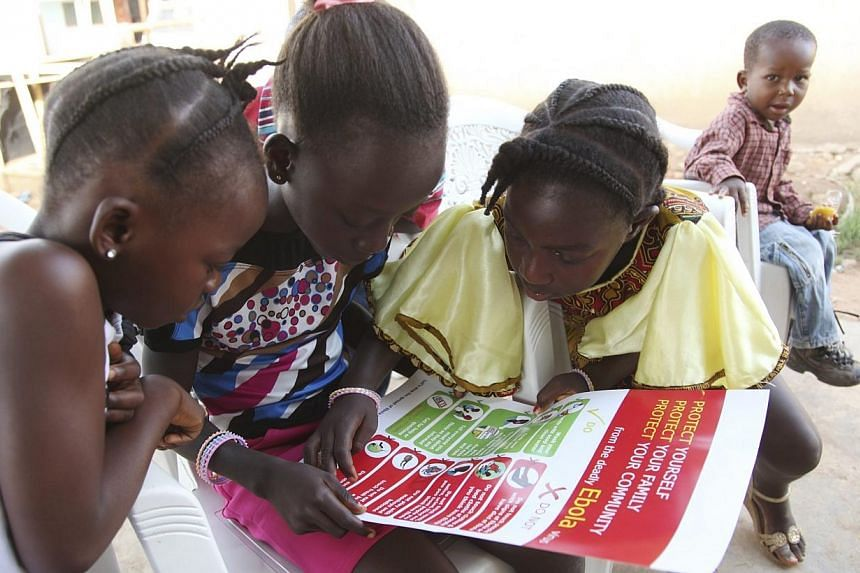 Girls look at a poster, distributed by UNICEF, bearing information on and illustrations of best practices that help prevent the spread of Ebola virus disease (EVD), in the city of Voinjama, in Lofa County, Liberia in this April 2014 UNICEF handout ph
