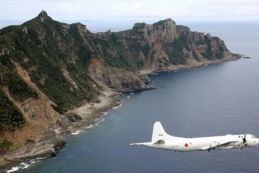 A Japan Maritime Self-Defense Force's PC3 surveillance plane flies around the disputed islands in the East China Sea, known as Senkaku in Japan and Diaoyu in China on Oct 13, 2011.Japanese fighter jets shadowed Chinese aircraft patrolling over
