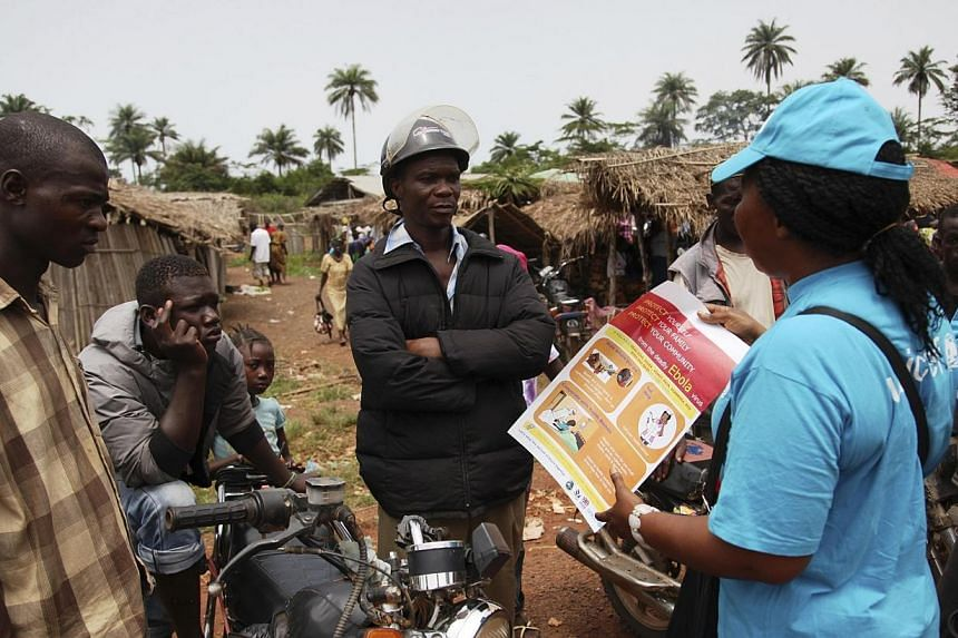 A UNICEF worker speaks with drivers of motorcycle taxis about the symptoms of Ebola virus disease (EVD) and best practices to help prevent its spread, in the city of Voinjama, in Lofa County, Liberia in this April 2014 UNICEF handout photo.Libe