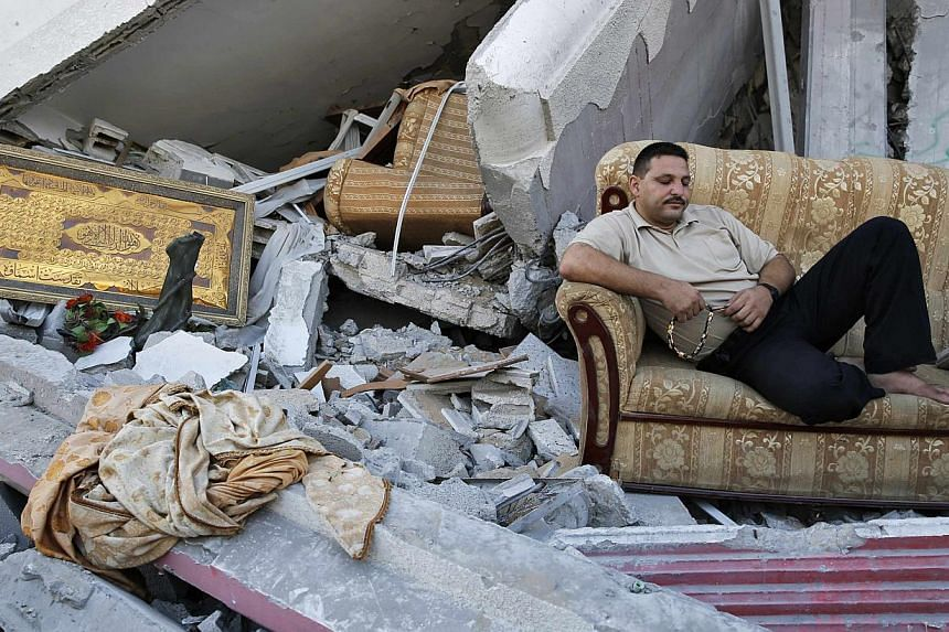 A Palestinian sits amid the ruins of destroyed homes in the Shejaia neighbourhood, which witnesses said was heavily hit by Israeli shelling and air strikes during an Israeli offensive, in Gaza City on Aug 6, 2014. -- PHOTO: REUTERS