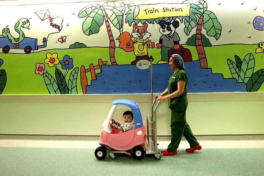 Nurse Jaslin Nah Siew Noy, 36, wheeling her patient, 27-month-old Clarence Lee Hao Cheng into the operating theatre using an unconventional method – a toy car. This is one of the ways that KK Hospital uses to calm young patients as there is usually