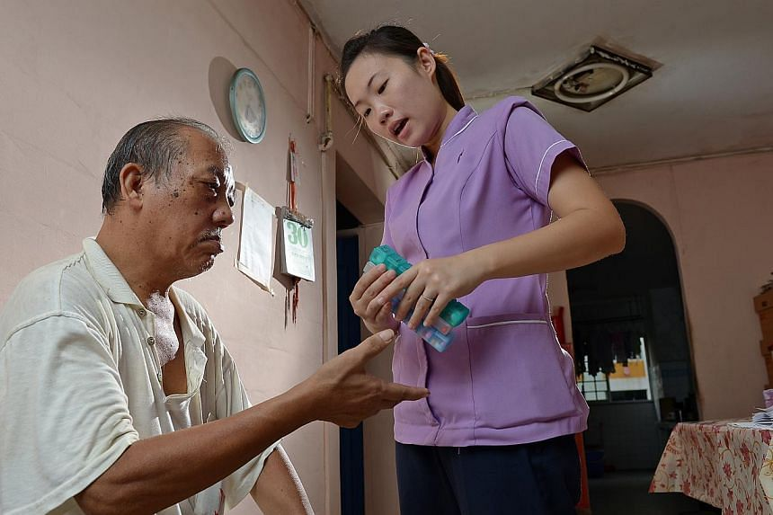 Home Nursing Foundation's senior staff nurse Chua Geok Fong sorting out the medication for her patient See Choon Bok. She visits him at home once every two weeks to ensure he is taking the right dosage. -- ST PHOTO: DESMOND WEE