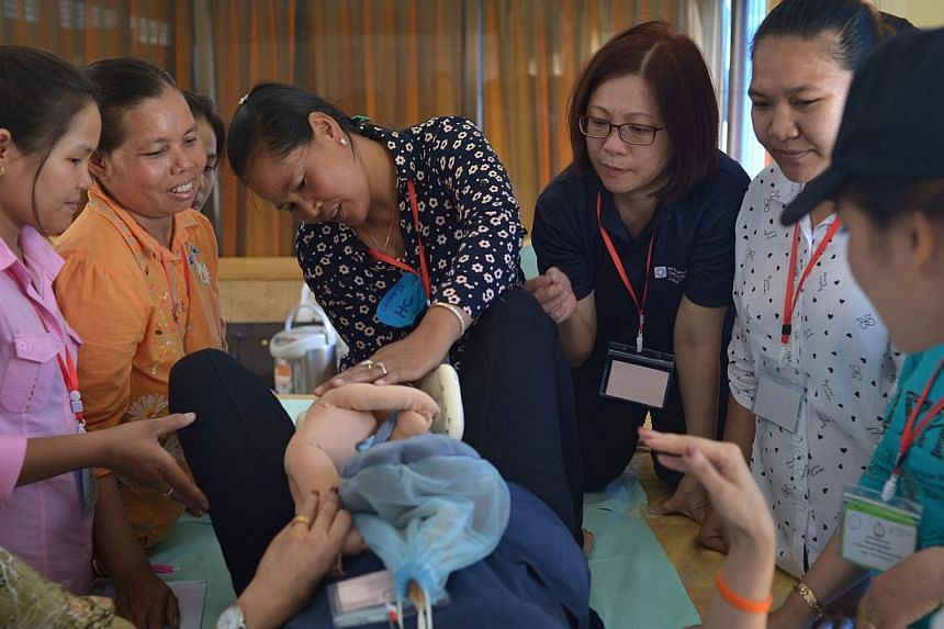 Ms Juay Siew Ngoh (third from right), a senior nurse manager at KK Hospital, conducting a training session in Cambodia for Cambodian midwives on the procedure of delivering a baby. -- ST PHOTO: CAROLINE CHIA