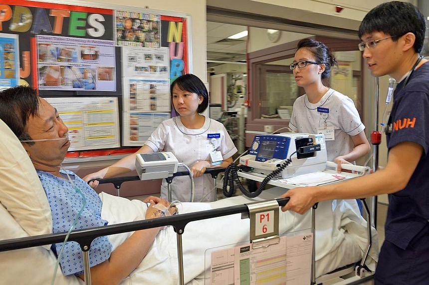 National University Hospital staff nurses Seow Wai Shin and Antoninette Goh and Dr Stephen So Ching-Tung moving a patient for a procedure to explore blockage of heart blood vessels. -- ST PHOTO: DESMOND WEE