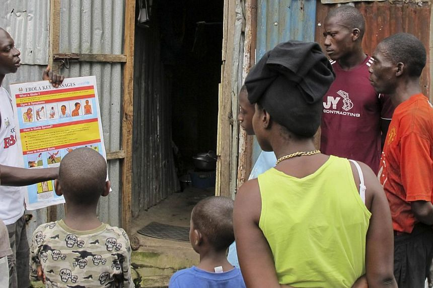 An outreach worker speaks with residents about the information on the symptoms of Ebola virus disease (EVD) and best practices to help prevent its spread, in Freetown, Sierra Leone in this Aug, 2014 handout photo provided by UNICEF Aug 6, 2014. -- PH