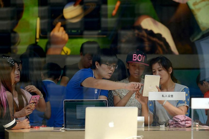 A salesman introduces products to customers at an Apple store in Beijing on Aug 8, 2014.Apple products such as laptops and tablets are not banned from Chinese government procurement lists, according to the country's chief procurement centre, re
