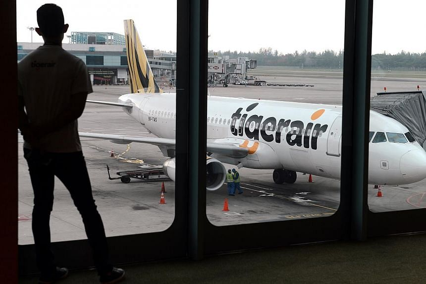 A Tigerair plane at Changi Airport on July 3, 2013.Budget carriers Tigerair and Scoot have received approval from Singapore's competition watchdog to work closely to plan flights, schedules and fares. -- PHOTO: ST FILE
