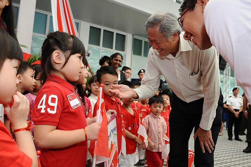 Minister for Defence Dr Ng Eng Hen (second right) and Minister of State for Defence Dr Mohamad Maliki Bin Osman interacting with children from Cherie Hearts @ Gombak after a ceremony celebrating Singapore's 49th birthday on Aug 8, 2014. -- PHOTO: MIN