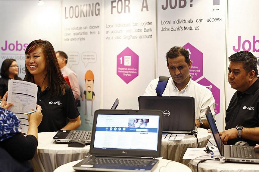 WDA career coaches help job applicants sift through the Jobs Bank website on 14 July, 2014. The portal now has more than 50,000 jobs for Singaporeans up for grabs. -- ST PHOTO: DESMOND LUI