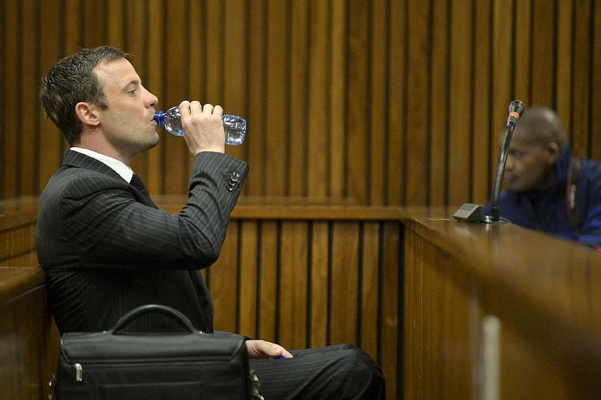 """South African Olympic and Paralympic sprinter Oscar Pistorius drinks from a bottle as he sits in the dock before the defence's final argument in the North Gauteng High Court in Pretoria on Aug 8, 2014.Pistorius' """"primal instincts"""" kicked in whe"""