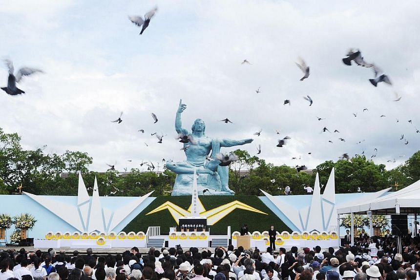 Pigeons fly around the peace statue during a memorial service for victims of the 1945 atomic bombing, at Nagasaki Peace Park on Aug 9, 2014.Tens of thousands marked the 69th anniversary of the US atomic bombing of Nagasaki on Saturday, Aug 9, 2