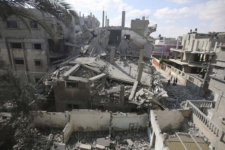 Palestinians look at the remains of a house, which witnesses said was hit by an Israeli air strike in Rafah in the southern Gaza Strip on Aug 9, 2014. Israeli warplanes kept up a punishing campaign of air strikes over Gaza, killing five Palestin