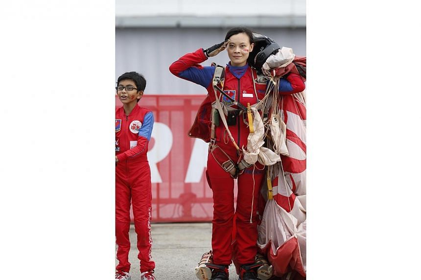 Third Warrant Officer Shirley Ng salutes after completing her jump during NDP 2014.-- ST PHOTO: KEVIN LIM