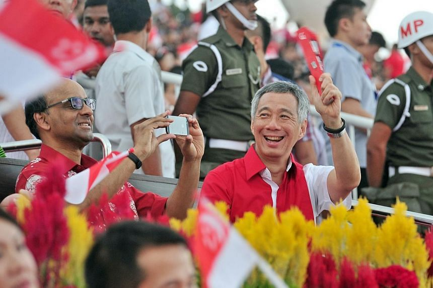Prime Minister Lee Hsien Loong and Deputy Prime Minister Tharman Shanmugaratnam at the National Day Parade 2014. -- ST PHOTO: STEFFI KOH