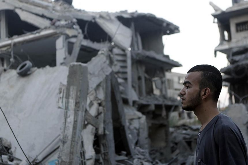A Palestinian man stands looking at destroyed buildings in the Jabalia refugee camp in the northern Gaza Strip on Aug 8, 2014. Israeli warplanes on Friday pounded targets across Gaza, killing at least five Palestinians, and militants fired dozens of