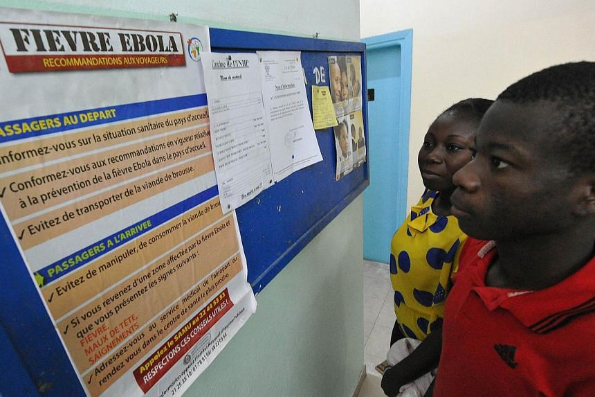 People read a poster bearing informations for travellers arriving in or departing from areas affected by the Ebola virus, on Aug 8, 2014 at the national public health institute in Abidjan. -- PHOTO: AFP
