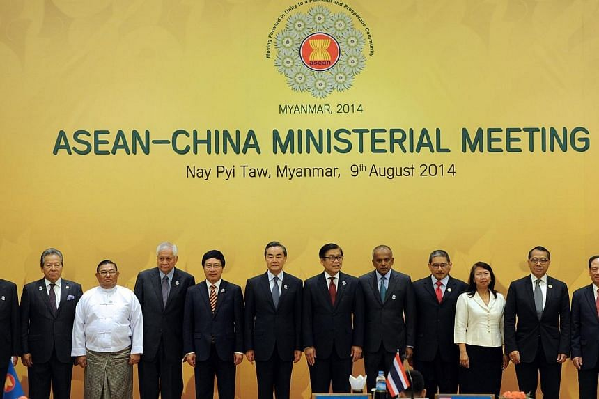 Chinese Foreign Minister Wang Yi (sixth from L) and ASEAN foreign ministers and officials pose for a photo prior to the ASEAN-China ministerial meeting at the Myanmar International Convention Center (MICC) in Naypyidaw on August 9, 2014. -- PHOTO: AF