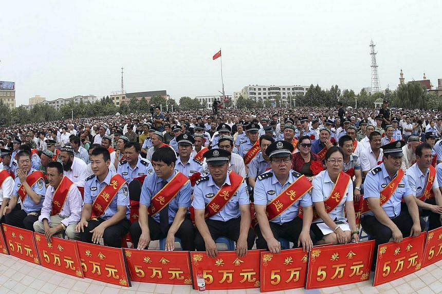 """Police wearing sashes hold placards during a ceremony to award those who the authorities say participated in """"the crackdown of violence and terrorists activities"""" in Hotan, Xinjiang Uighur Autonomous Region on Aug 3, 2014.Chinese authorities sa"""