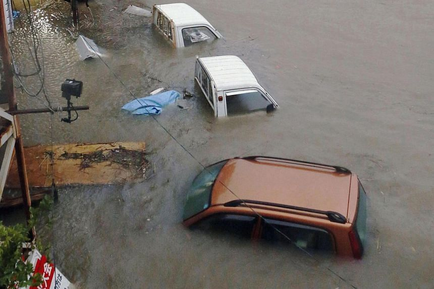 Stranded cars are seen in floodwater caused by Typhoon Halong in Kochi, western Japan in this photo taken by Kyodo on Aug 10, 2014.Typhoon Halong slammed into western Japan on Sunday, leaving dozens of people injured while the coastguard search