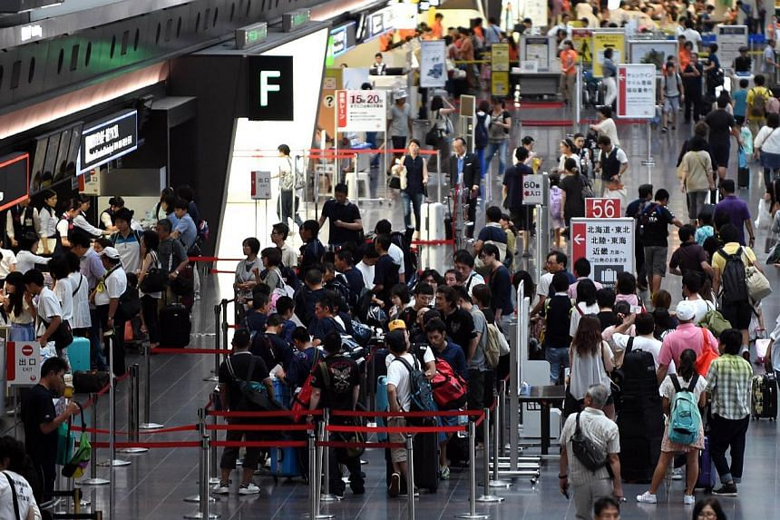 Passengers line up to check in for their flights at the Haneda airport terminal in Tokyo on Aug 10, 2014. -- PHOTO: AFP