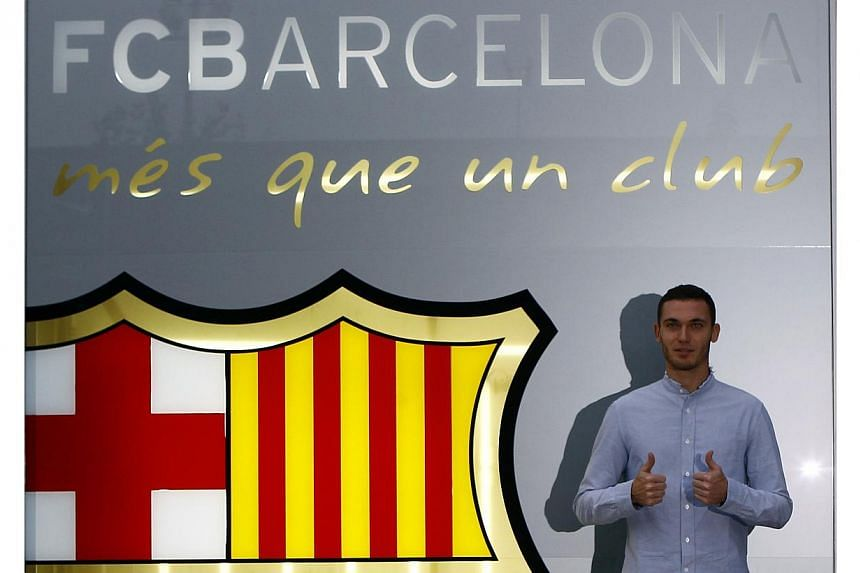 Belgium soccer player Thomas Vermaelen poses next to a logo at his arrival at FC Barcelona's offices in Barcelona, on Aug 9, 2014. -- PHOTO: REUTERS