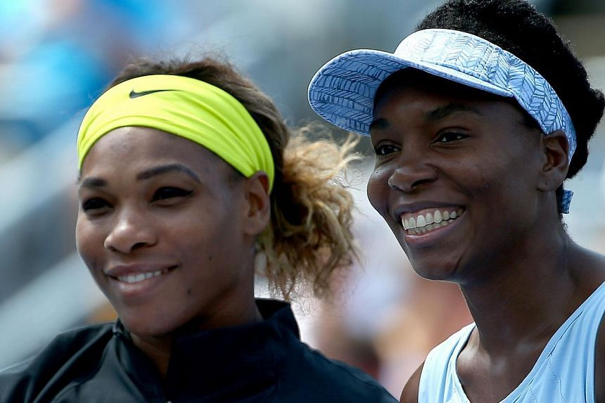 Serena Williams of the USA and Venus Williams (right) of the USA pose before their women's semifinals match in the Rogers Cup at Uniprix Stadiumin Montreal, Canada on Aug 9, 2014 . -- PHOTO: AFP