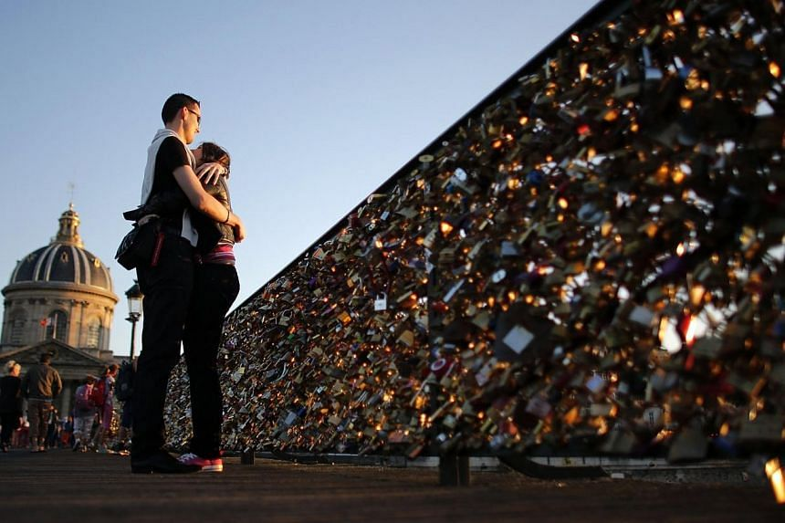 A couple embraces during sunset on the Pont des Arts with its fence covered with padlocks clipped by lovers over the River Seine in Paris, in this August 10, 2013 file photo. -- PHOTO: REUTERS