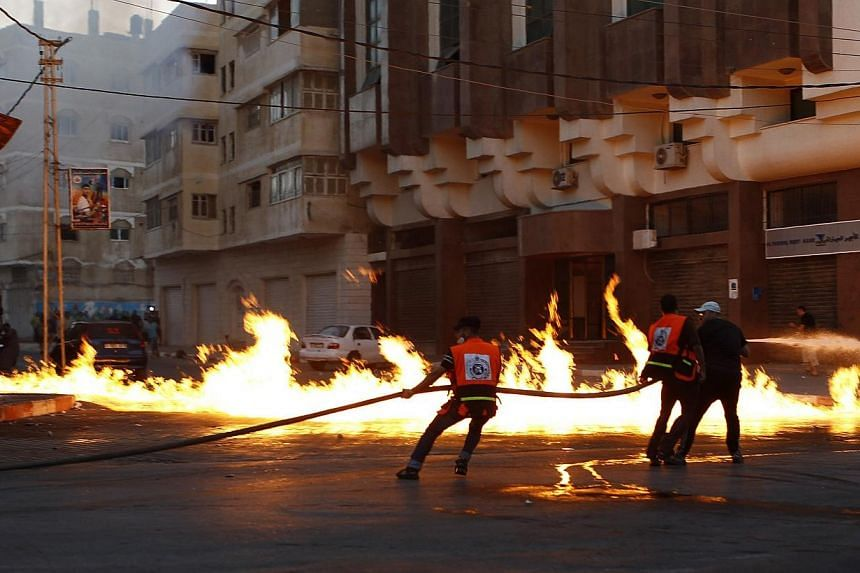Firefighters try to extinguish a fire that witnesses say was caused by an Israeli air strike in Gaza City August 10, 2014.Israeli negotiators were due in Cairo on Monday for talks on ending a month-old Gaza war with Palestinian militants, an Is