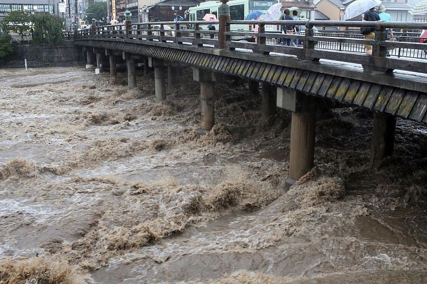 This picture taken on August 10, 2014 shows muddy water running under a wooden made bridge in Kyoto, western Japan. -- PHOTO: AFP