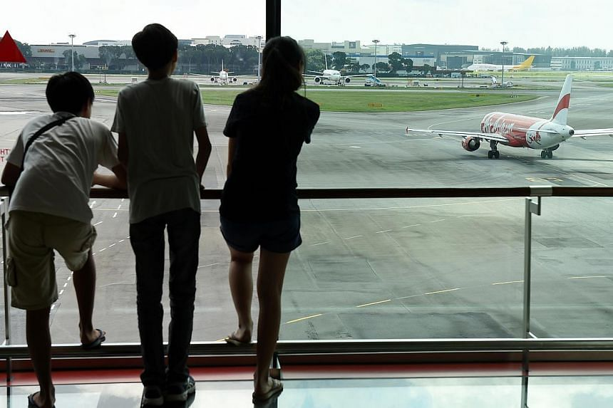 Members of the public looking at an aircraft taxiing out from the aircraft parking stands at Changi Airport. -- PHOTO: ST FILE